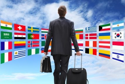 Homem usando um terno preto, de costas com uma mala preta na mão direita e uma pasta preta na mão esquerda. Na frente do homem tem um céu azul e bandeiras de todos os países representando um mundo infinito de possibilidades.